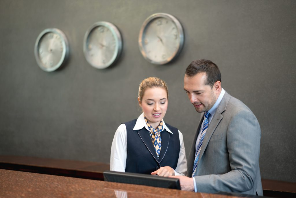 Hotel manager talking to woman at the front desk